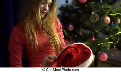beautiful young girl puts on a Santa hat on her favorite toy...