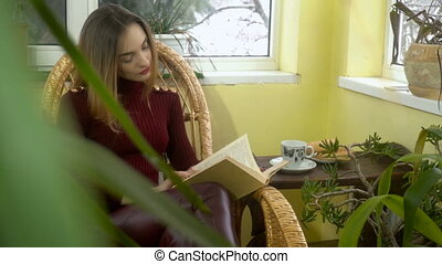 beautiful young girl reading a book in a wicker rocking chair and looking out the window with lots of green plants around