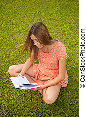Beautiful young girl reading a book sitting on the grass