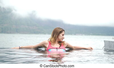 Beautiful young girl relaxed in swimming pool in a blue and...