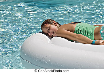 Beautiful Young Girl Relaxing in a Pool