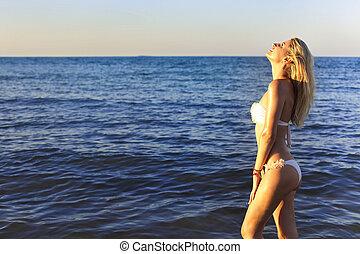 Beautiful young girl relaxing on a beach of tropical ocean