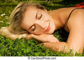 Beautiful young girl relaxing on a meadow