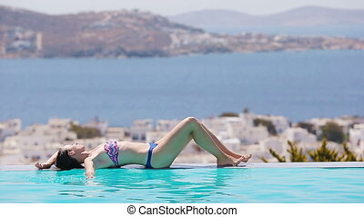 Beautiful young girl relaxing on the edge of swimming pool outdoors
