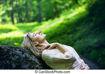 girl resting in a forest on the rock