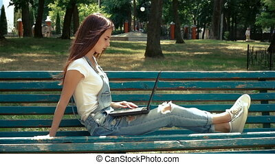 young girl resting on a bench in the Park and looking at laptop