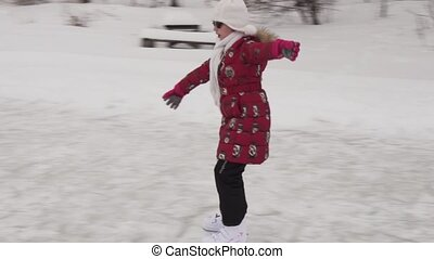 Beautiful young girl riding on figure skates at outdoor rink...