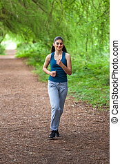 Beautiful young girl running in green park on sunny summer day