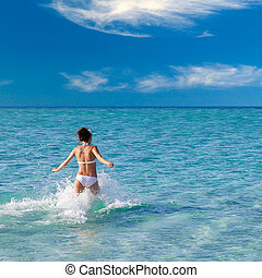 Beautiful young girl running into the water of sea