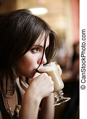 Beautiful young girl sipping coffee lattee. Shallow DOF.