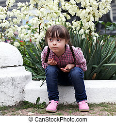 Beautiful young girl siting on flowers background