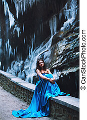Beautiful young girl sits on a stone hedge against a background of a mountain massif and glacier