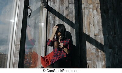 Beautiful young girl sits on a sunny winter day at the window and holds in her hands a hot cup of tea