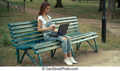 beautiful young girl sitting in a park with a laptop and drink coffee