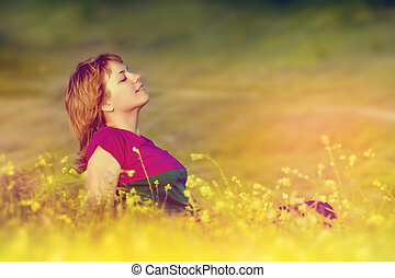 Beautiful young girl sitting in the grass at sunset and enjoys