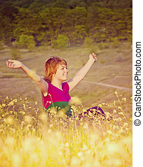 Beautiful young girl sitting in the grass at sunset holding up his hands to the sky