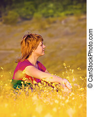 Beautiful young girl sitting in the grass at sunset