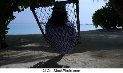 Beautiful young girl sitting on a swing on the beach. Sea background.
