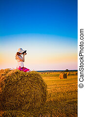 Beautiful young girl sitting on haystack