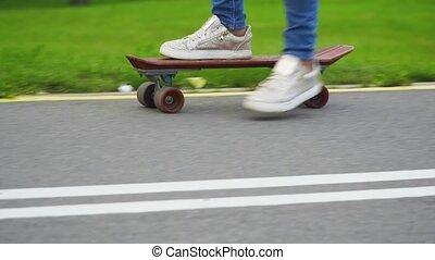 Beautiful young girl skates on skateboard at sunset