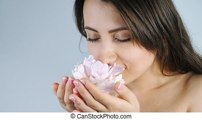 Beautiful young girl smelling the flower - Young attractive...