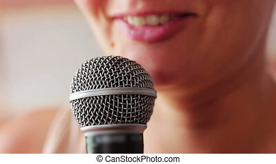 Beautiful young girl speaks in vocal, hand-held dynamic microphone.Mouth girl in headphones speaks into the microphone in the studio close up
