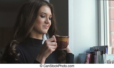 Beautiful young girl standing next to the window and drinking coffe.