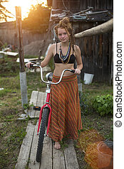 Beautiful young girl standing with a Bicycle in the village during sunset.