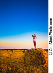 Beautiful young girl staying on haystack