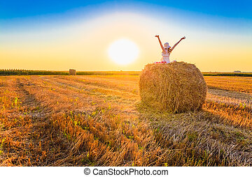 Beautiful young girl staying on haystack in sunny day