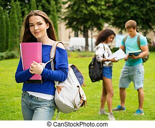 Beautiful young girl student in a city park on summer day