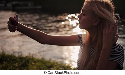 Beautiful young girl taking selfie at sunset. HD
