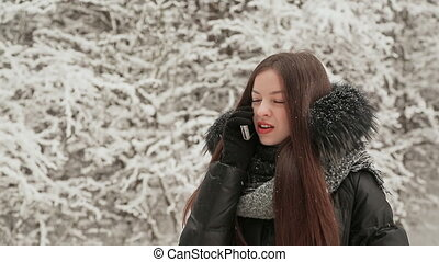 Beautiful young girl talking on the phone on the background of fir trees in the snow. Snow falls. Winter. Outdoor winter portrait.