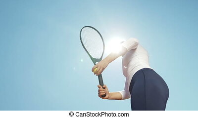 Beautiful young girl tennis player woman serving ball with racket outdoor with sun behind her