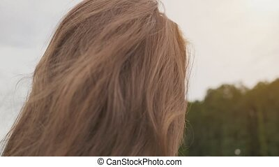 Beautiful young girl touches her hair in nature. Sensual portrait close-up. Youth. Beauty. Summer.