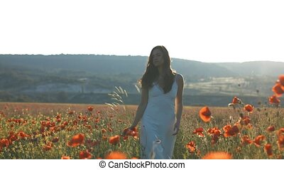 Beautiful young girl walking in poppy field