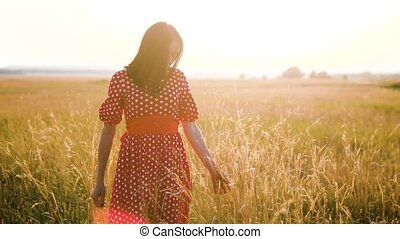 Beautiful young girl walking on field with wildflowers,...