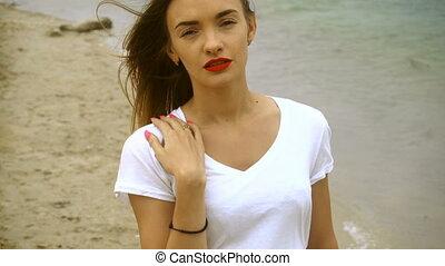 beautiful young girl walks on the beach