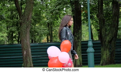 beautiful young girl walks with colourful balloons