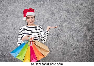 Beautiful young girl wearing a Santa hat holding lots of shopping bags