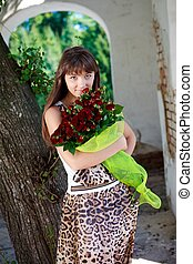 Beautiful young girl with a bouquet of red roses