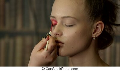 Beautiful young girl with a stylist doing makeup in a beauty salon