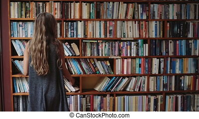 Beautiful young girl with book in hand walks along the bookshelves