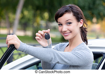 Beautiful young girl with car key in hand