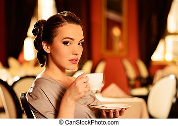 Beautiful young girl with cup of coffee alone in a restaurant