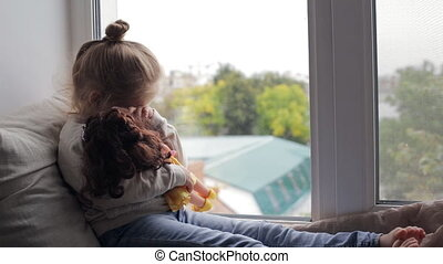 Beautiful young girl with doll sitting on a window sill at...