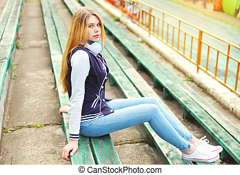Beautiful young girl with headphones sitting listens to music in city park