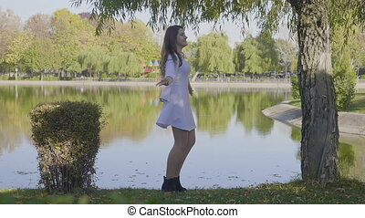 Beautiful young girl with long hair dressed in white clothes spinning near to a lake in park on an autumn day in slow motion