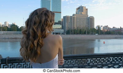 Beautiful young girl with long hair in a white dress is standing on the city waterfront.