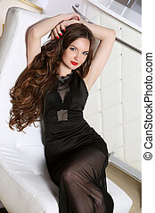 Beautiful young girl with long hairstyle curly hair. Elegant woman lying on modern chair in white interior. Wavy hair. Red lips makeup.